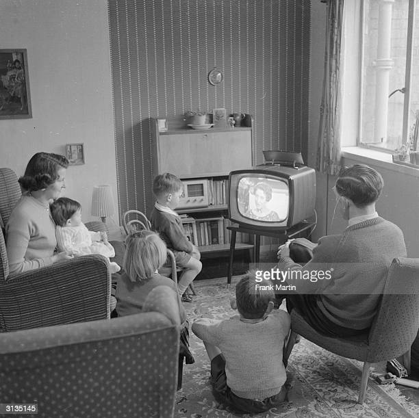 Joan Evans watches television with her husband and four children at their new home in the new town of Harlow Essex