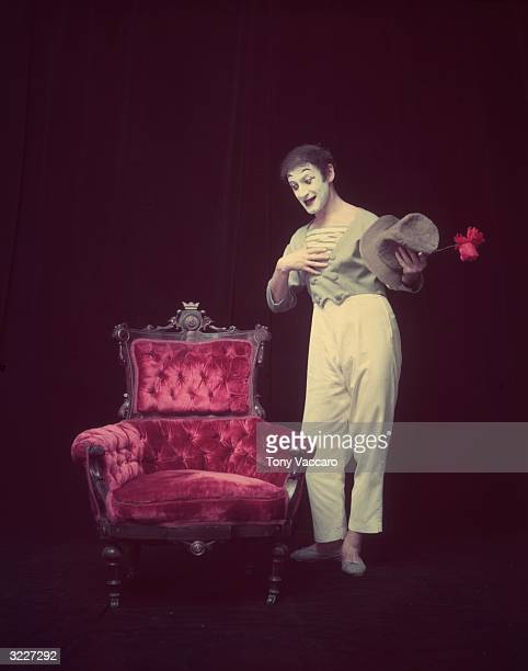 Full-length studio portrait of French actor and pantomimist Marcel Marceau, in costume, standing beside an arm chair with a flower in hand and...