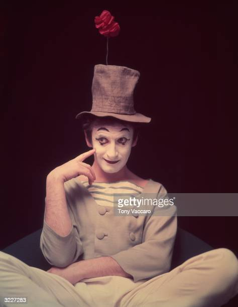 Studio portrait of French actor and pantomimist Marcel Marceau, in costume, sitting cross legged with his finger on his cheek and an artificial...