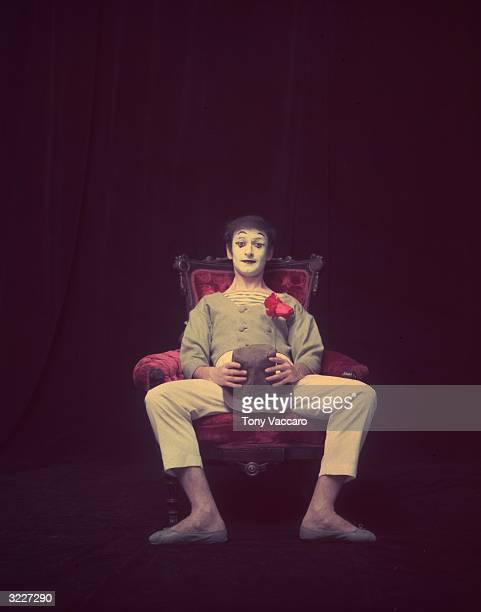 Studio portrait of French actor and pantomimist Marcel Marceau, in costume, sitting in a wooden arm chair with his hat and an artificial flower in...