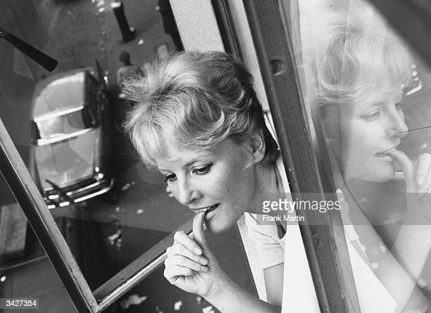 British singer and actress Petula Clark looking out of a window