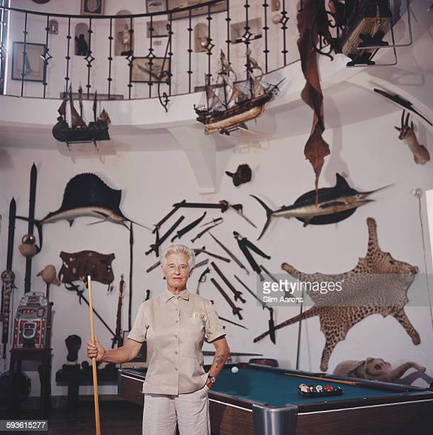 Marion Barbara Carstairs aka Joe Carstairs stands amidst her trophies stuffed fish leopard skin and weapons plus a pool table in her museum on her...