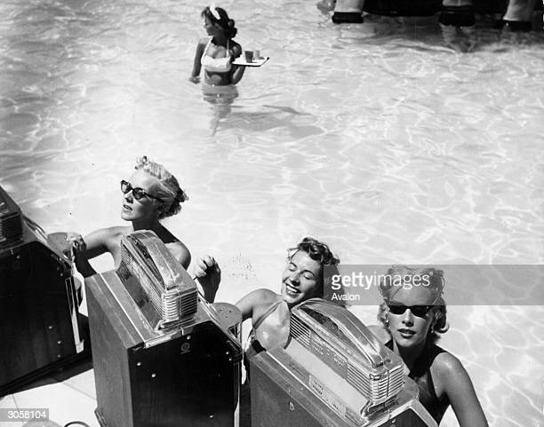 Three women play the slot machines at a swimming pool casino in the Sands Hotel Las Vegas Nevada A wading waitress with a tray makes her way towards...