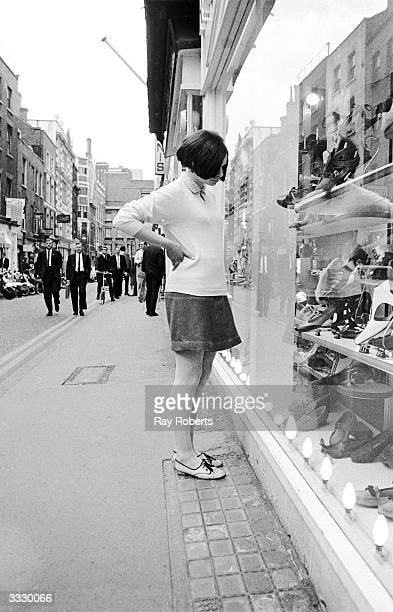 A young woman windowshopping for shoes in London