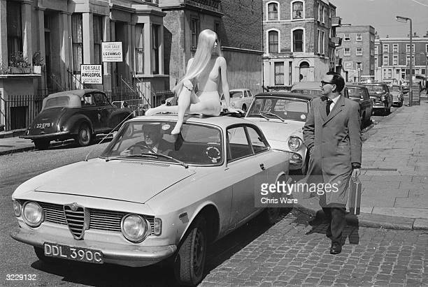 A pedestrian's attention is caught by a fibreglass tailors's dummy made by Gem's Ltd sitting on top of a car in Lancaster Road west London