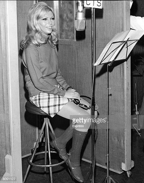 Fulllength view of American singer Nancy Sinatra sitting on a stool in front of microphone and a music stand in a studio while recording 'You Only...