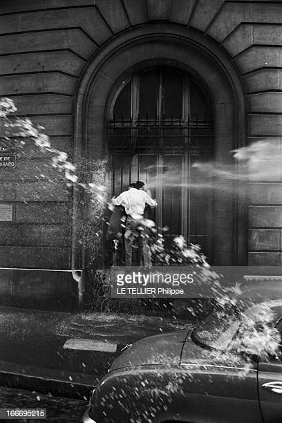 May 1968 A Paris en France en mai 68 les forces de l'ordre utilisent des canons à eau pour disperser deux manifestants attachés à la grille d'une...