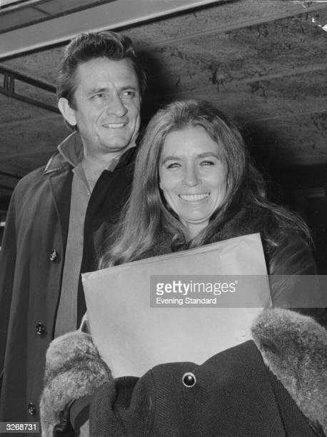 American country singer and songwriter Johnny Cash at London Airport with his wife June Carter Cash of the Carter Family group