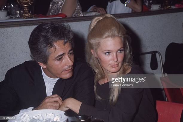 Married American actors John Derek and Linda Evans sit together in close proximity during an Emmy Awards ceremony. Evans wears her long blonde hair...