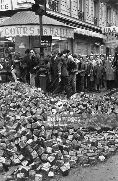 Parisians resume the business of everyday life clambering over rubble left in the streets from the student riots