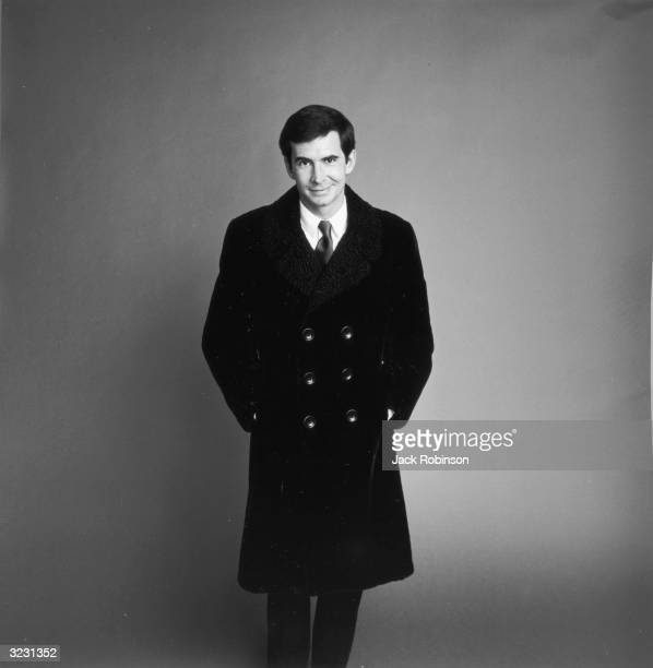 Studio portrait of American actor Anthony Perkins posing in a doublebreasted Persian lamb overcoat for Vogue magazine