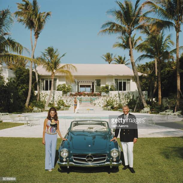 Alvin and Lilly Fuller outside their new home in Palm Beach Florida pose with their fashionable European sports car the Mercedes 190SL