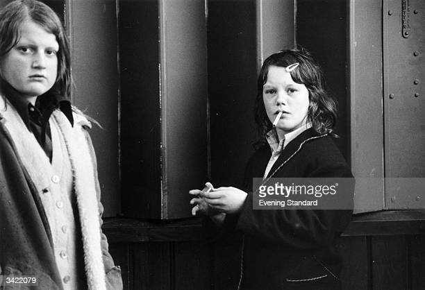 A schoolgirl smoking an illicit cigarette in Hyde Park London as her friend stands guard
