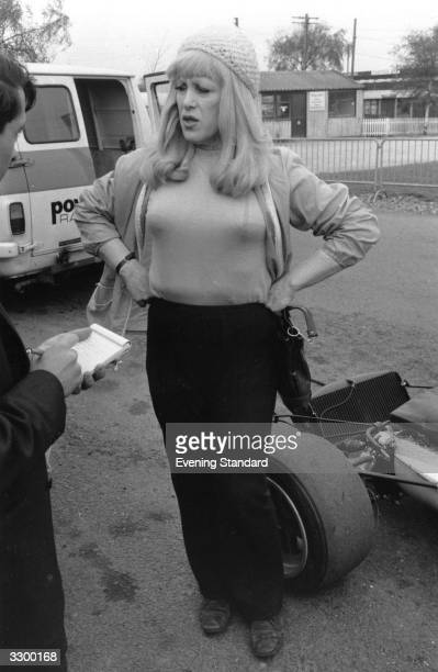 Roberta Cowell by a racing car gives an interview.