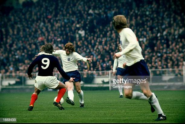 Alan Ball of England takes on Kenny Dalglish of Scotland during the international match against Scotland played at Wembley Stadium in London England...