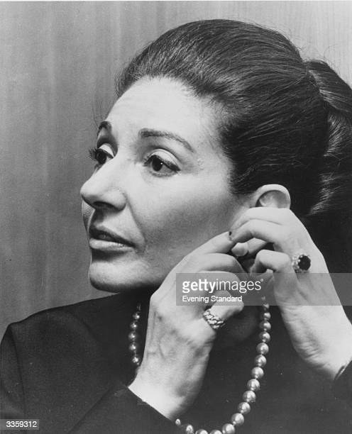 American opera singer Maria Callas putting on jewellery.