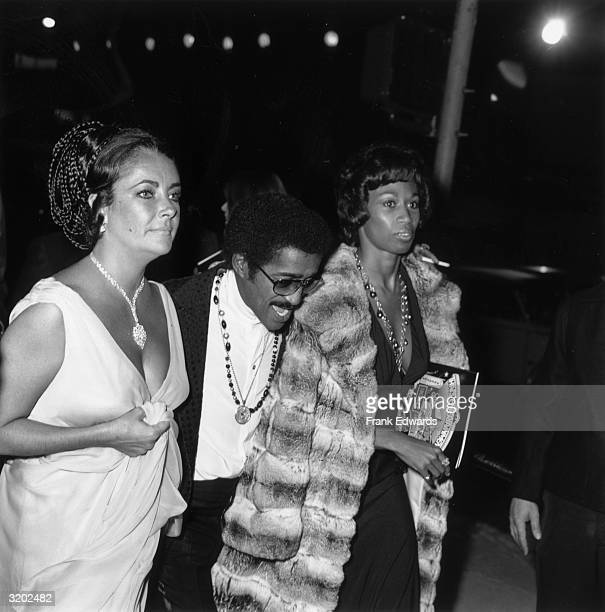 LR Britishborn actor Elizabeth Taylor American entertainer Sammy Davis Jr and his wife Altovise Gore attend the premiere of director Jack Haley Jr's...