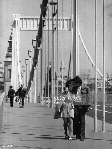 A couple kissing as they walk over the Elizabeth Bridge in Budapest Hungary
