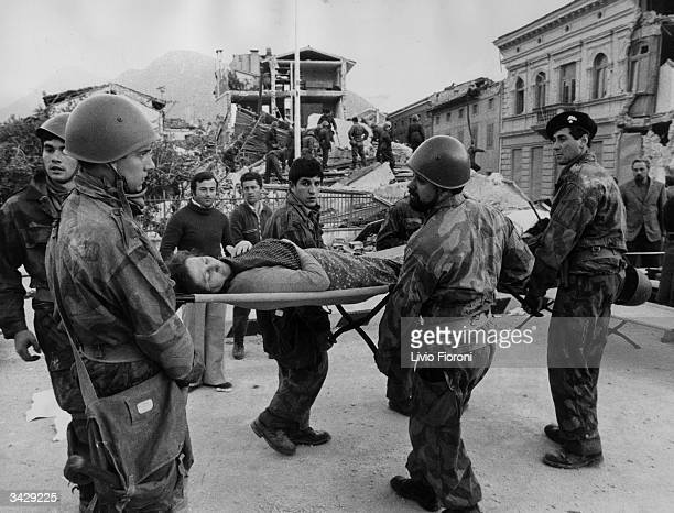 Italian soldiers carry a woman on a stretcher to a place of safety after she was dug from the remains of her home after an earthquake in Udine which...