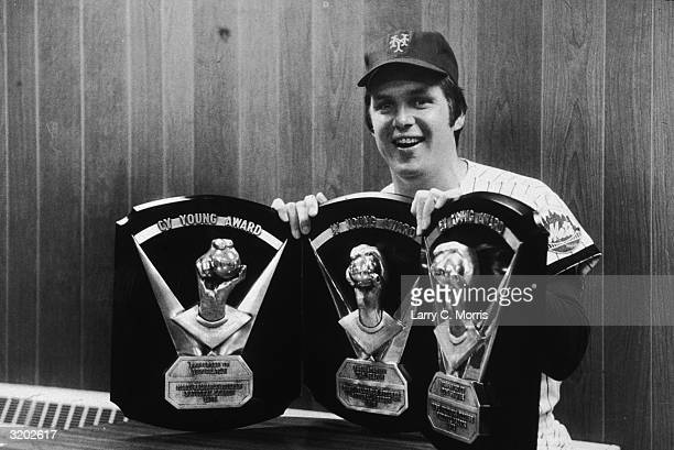 Portrait of American baseball player Tom Seaver wearing a New York Mets uniform smiling while posing with the Cy Young Awards he won for the 1969 and...