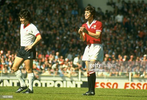 Martin Buchan of Manchester United and Kevin Keegan of Liverpool in action during the FA Cup final at Wembley Stadium in London Manchester United won...