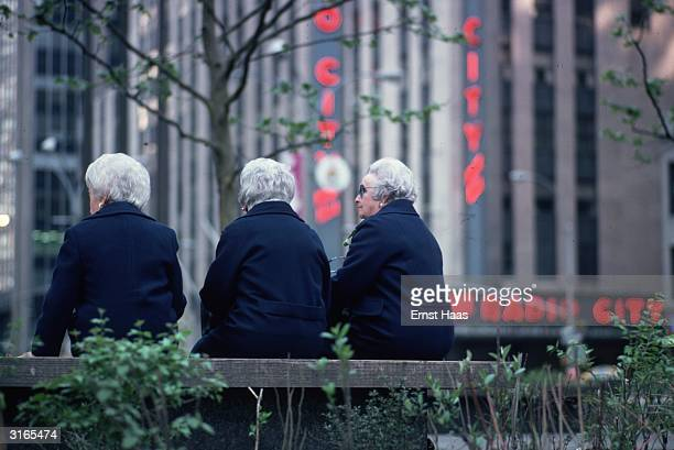 Three grey haired old women dressed alike in dark blue coats sit on a bench in a square opposite Radio City in New York