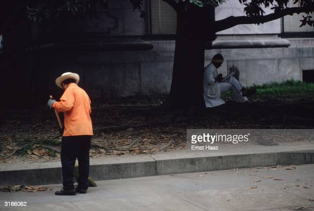 A man in a white suit sits under a tree reading while a street sweeper clears up the leaves in New Orleans Louisiana