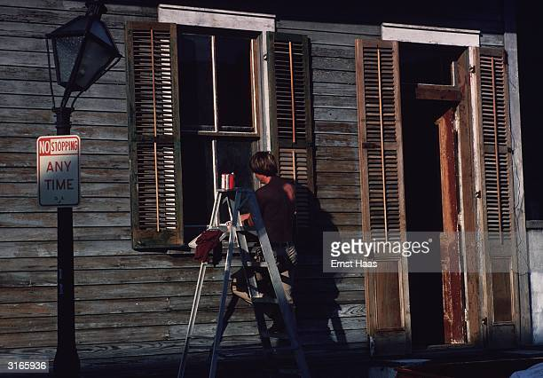 A young man getting ready to paint the windows of a rundown clapboard house in New Orleans Louisiana