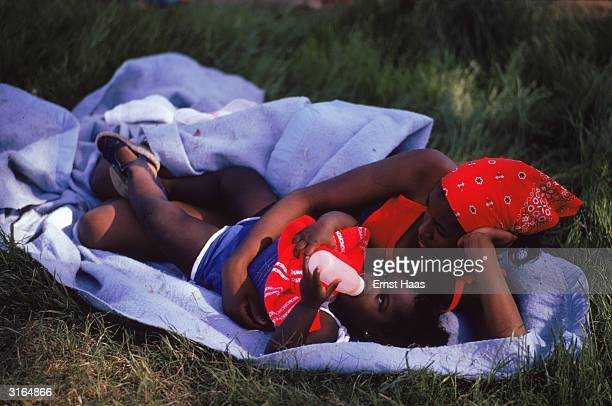 Drinking from a feeding bottle a little girl lies on a blanket in the grass wrapped in her mother's arms