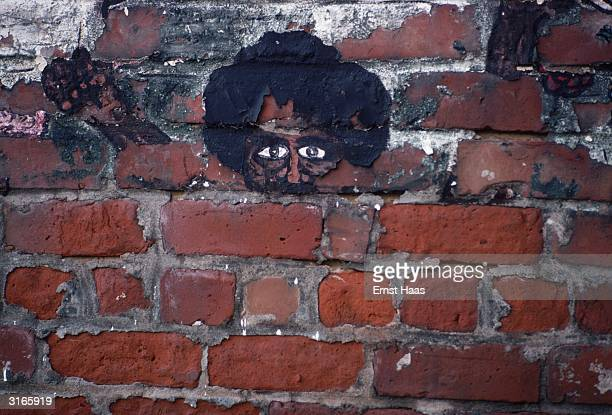 Head of a guitarist on a wall in New Orleans Louisiana is flaking off the bricks on which it is painted