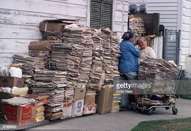 Two women chat by a pile of waste paper stacked into bundles on a street in New Orleans Louisiana