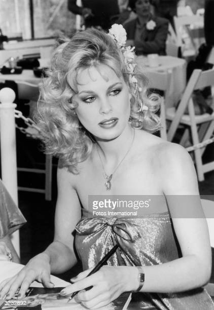 Canadian model and actor Dorothy Stratten 'Playmate of The Year' for 1980 holding a pen over a copy of Playboy magazine during a reception at the...