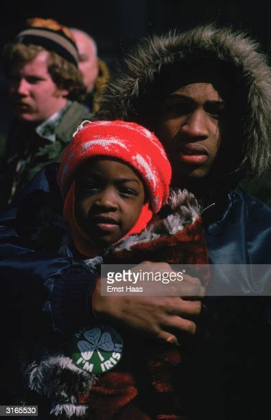 A young man and a child wrapped up against the cold in New York The child wears a badge stating 'I'm Irish'