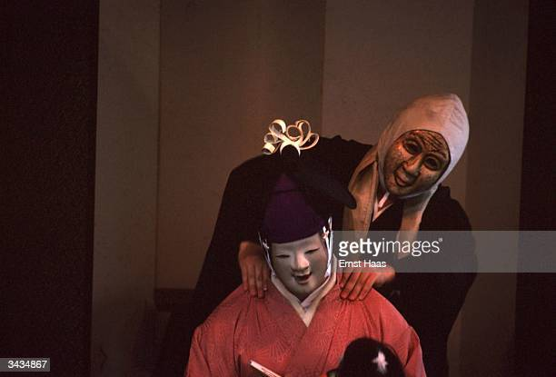 Masked actors in a Noh comedy performed in Kyoto Honshu Japan One wearing a 'happy' mask is giving another a shoulder massage