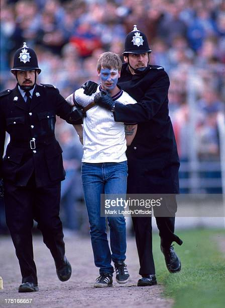 06 May 1985 Football League Div 1 Notts County v Manchester City a City fan is escorted out of the ground by two police officers one has his...