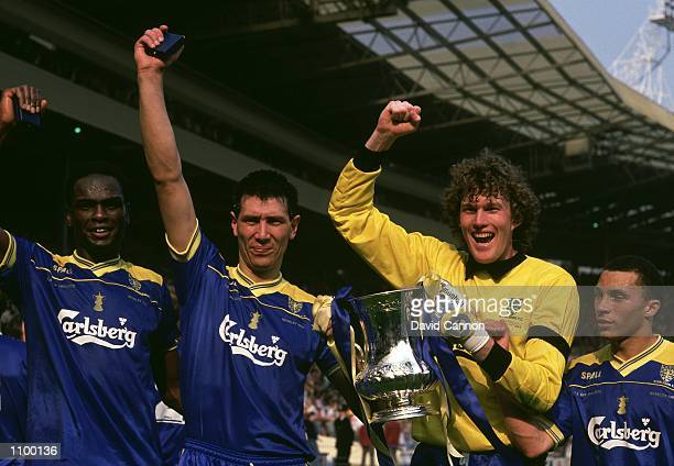 Eric Young Lawrie Sanchez Dave Beasant and Terry Phelan of Wimbledon celebrate with the trophy after their victory in the FA Cup final against...