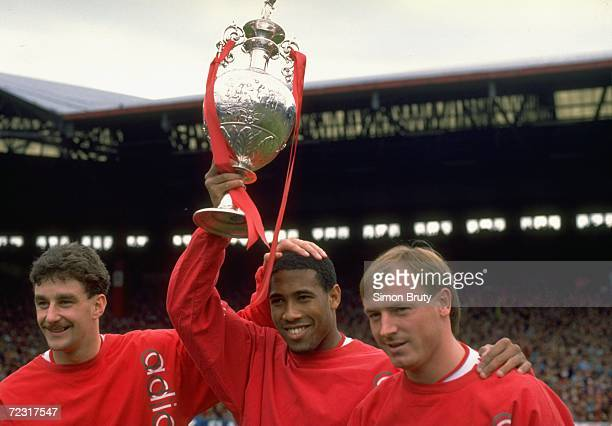 John Aldrige John Barnes and Steve McMahon of Liverpool hold the League Champions trophy aloft before the Barclays League Division One match against...