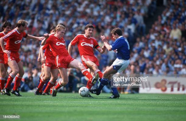 May 1989 F.A. Cup Final - Liverpool v Everton, John Aldridge and Steve Staunton combine to tackle Kevin Sheedy with studs showing.