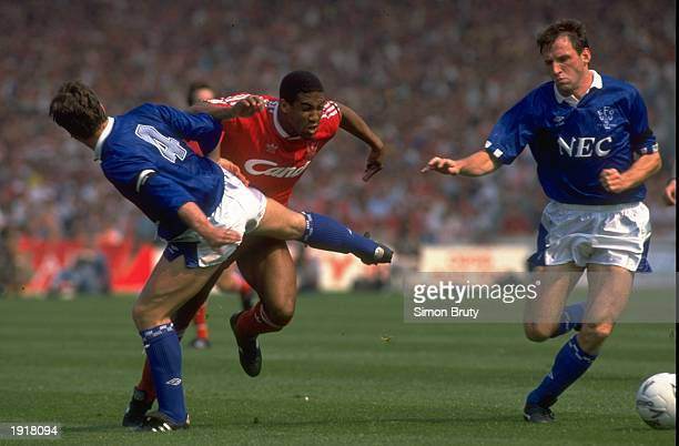 Kevin Ratcliffe of Everton brings down John Barnes of Liverpool as Dave Watson gains possession of the ball during the FA Cup final at Wembley...