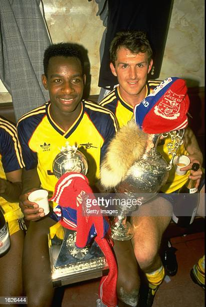 Michael Thomas and Martin Hayes of Arsenal hold the trophies after their victory in the League Division One match against Liverpool at Anfield in...