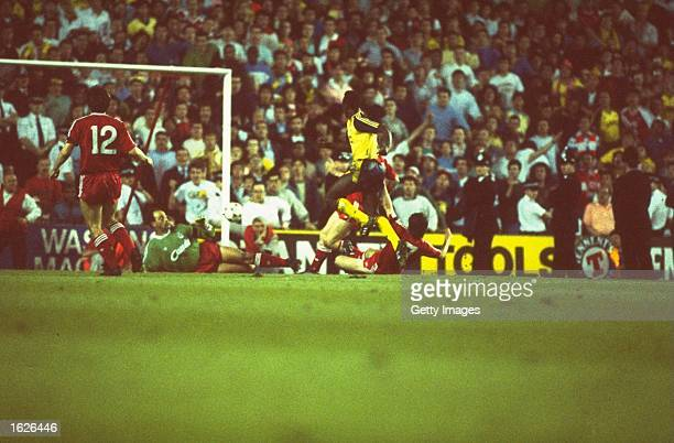 Michael Thomas of Arsenal defeats goalkeeper Bruce Grobbelaar of Liverpool to score their second title clinching goal during the League Division One...