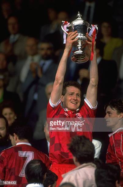 Brian Irvine of Aberdeen holds the trophy aloft after their victory in the Scottish Cup Final against Celtic at Hampden Park in Glasgow Scotland The...