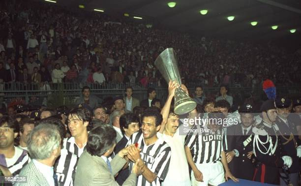 Sergei Aleinikou of Juventus holds aloft the trophy after their victory in the UEFA Cup Final second leg match against Florentina in Avellino Italy...