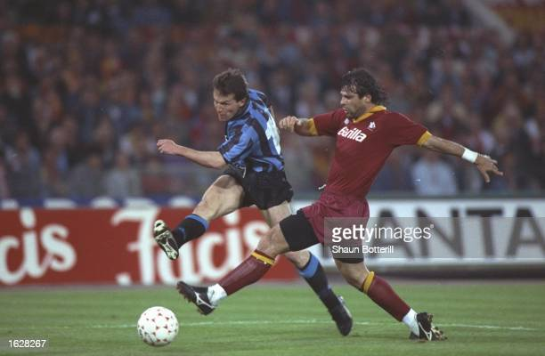 Lothar Matthaus of Inter Milan takes a shot at goal while Sabastiano Nela of AS Roma tries to intercept during the UEFA Cup Final second leg match at...