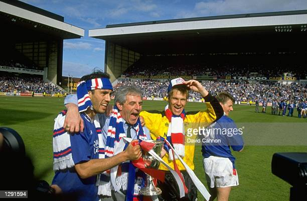 Mark Hately Walter Smith and Chris Woods of Rangers celebrate with the trophy after winning the Scottish Premier League match against Aberdeen at the...