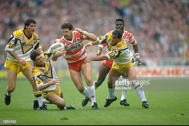 Gene Miles of Wigan is tackled by Keith England of Castleford during the Challenge Cup final at Wembley Stadium in London Wigan won the match 2812...