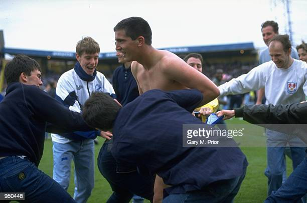 Andy Roberts of Millwall is stripped by fans after the League Division One match against Bristol Rovers Millwall's final game at the Den in London...