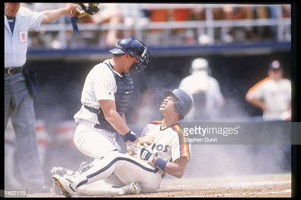 Catcher Dan Wolters of the San Diego Padres tries to tag out infielder Andujar Cedeno of the Houston Astros at Jack Murphy Stadium in San Diego...