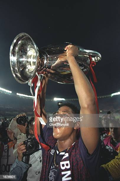 Patrick Kluivert of Ajax raises the trophy in celebration after their victory in the European Cup Final against AC Milan in Vienna Austria Ajax won...