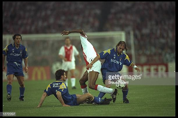 Antonio Conte and Ciro Ferrera of Juventus challenge Nwankwo Kanu of Ajax during the European Cup Final in Amsterdam Netherlands The game went to...